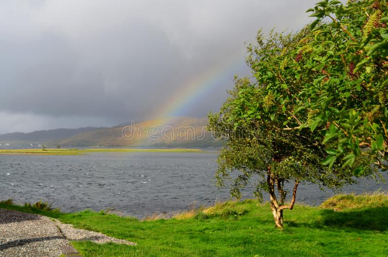 Hisnande sikt av Kylen av Lochalsh med en regnbåge fotografering för bildbyråer