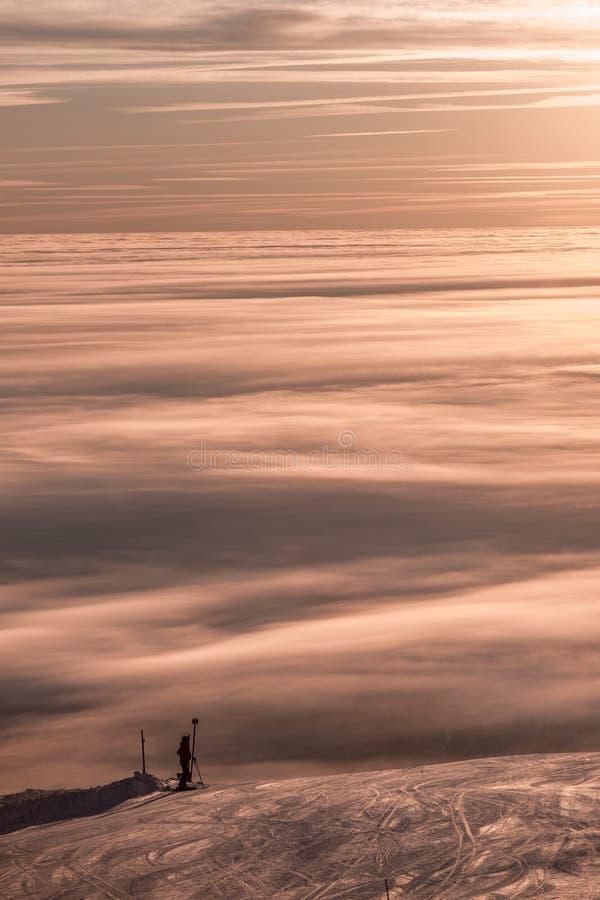 Hisnande solnedgång, fantastisk himmel, moln som drömmer och skidar och att koppla av överst av berget royaltyfri fotografi