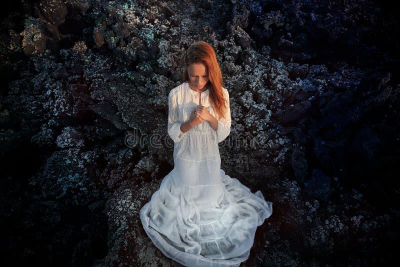 Hisnande stående av rödhårig mankvinnan i den vita klänningen som ber på kullen breathink med stängda ögon Lanzarote kanariefågel royaltyfri fotografi