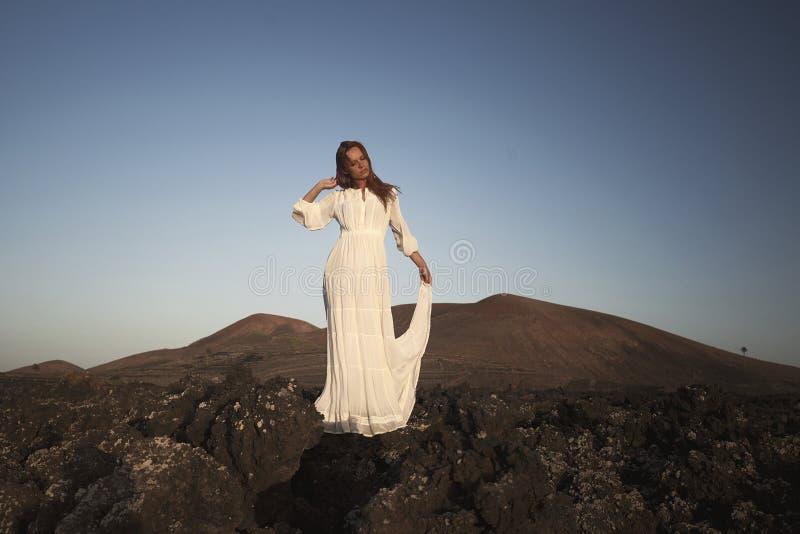 Hisnande stående av rödhårig mankvinnan på kullen i den vita klänningen blåsigt väder breathink med stängda ögon kanariefågelö la arkivfoto