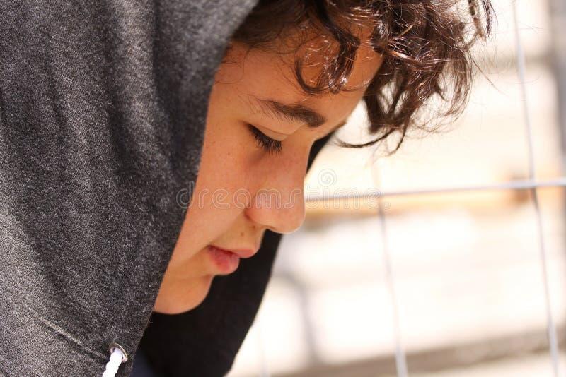 Hispânico incomodado triste 13 de velha escola anos de adolescente do menino que veste um levantamento do hoodie exterior - ascen foto de stock royalty free