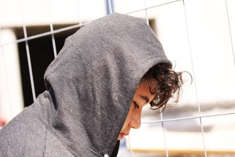 Hispânico incomodado triste 13 de velha escola anos de adolescente do menino que veste um levantamento do hoodie exterior - ascen fotos de stock royalty free