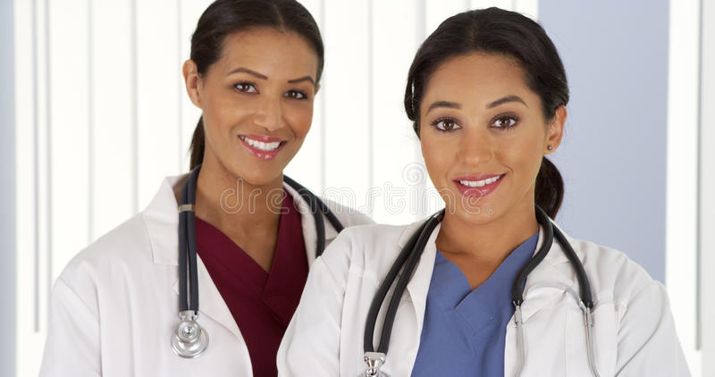 Hispanic and African American medical doctors looking at camera royalty free stock photo