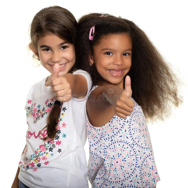 Hispanic and african-american small girls doing the thumb up sign. Cute hispanic and african-american small girls doing the thumb up sign and smiling - Isolated stock photography