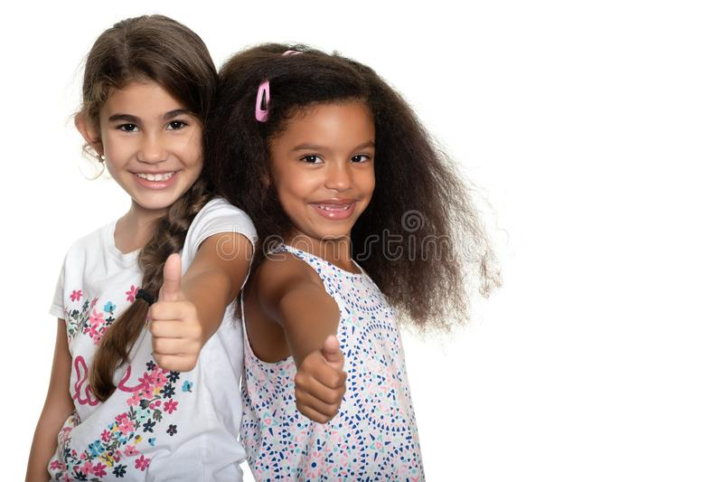 Hispanic and african-american small girls doing the thumb up sign. Cute hispanic and african-american small girls doing the thumb up sign and smiling - Isolated royalty free stock photography