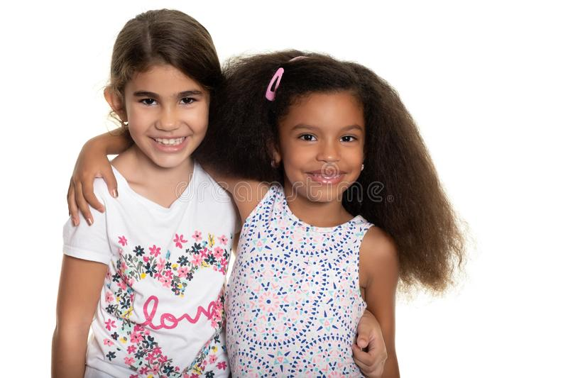 Hispanic and african american small girls hugging on a white background. Hispanic and african american small girls hugging - Isolated on white royalty free stock photography