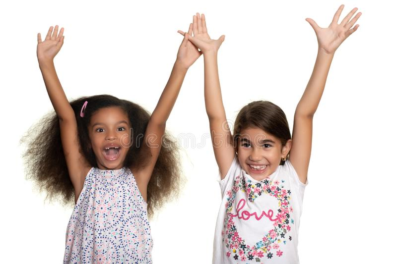 Hispanic and african-american small girls laughing and raising their arms. Isolated on white royalty free stock photography