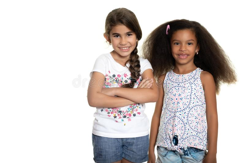 Hispanic and african-american small girls standing together and. Cute hispanic and african-american small girls standing together and smiling - Isolated on white royalty free stock image