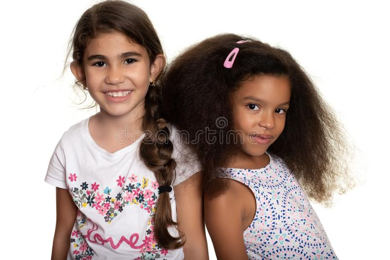 Hispanic and african-american small girls standing together and smiling. Cute hispanic and african-american small girls standing together and smiling - Isolated stock photography
