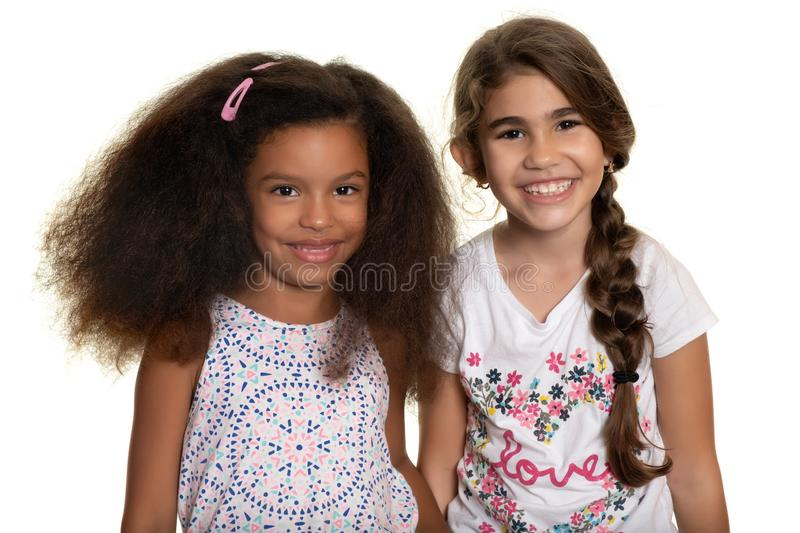 Hispanic and african-american small girls standing together and smiling. Cute hispanic and african-american small girls standing together and smiling - Isolated royalty free stock image