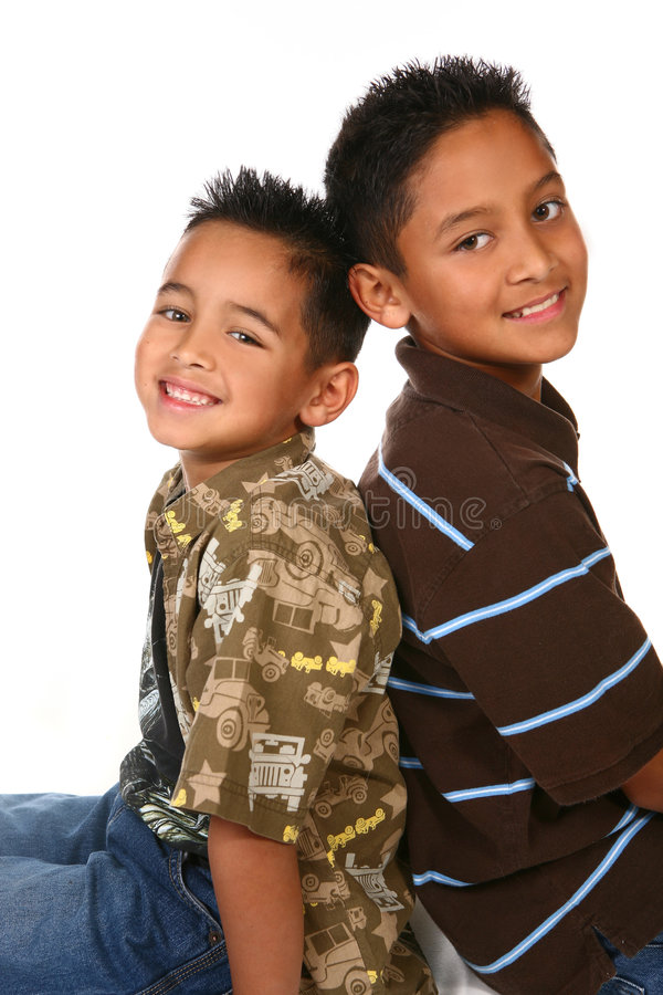 Hispanic American Brothers Sitting and Smiling. Hispanic American Brothers Sitting With Their Backs Touching While Smiling stock photo