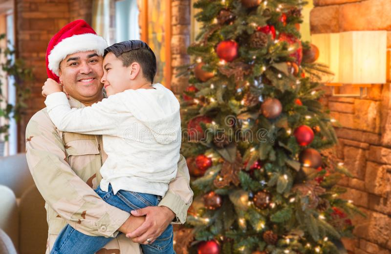 Hispanic Armed Forces Soldier Wearing Santa Hat Hugging Son. In Front Christmas Tree stock image