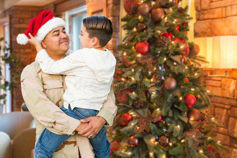 Hispanic Armed Forces Soldier Wearing Santa Hat Hugging Son. In Front Christmas Tree royalty free stock photo