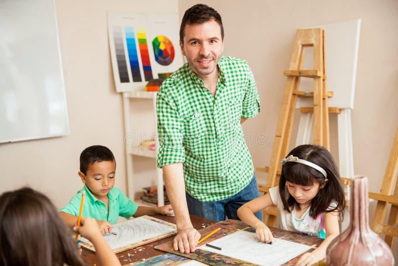 Hispanic art teacher with his students stock image