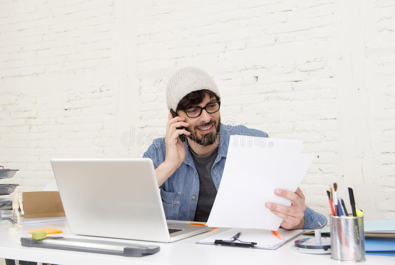 Hispanic attractive hipster businessman working at home office using mobile phone. Corporate portrait of young Hispanic attractive hipster businessman on his 30s royalty free stock photo