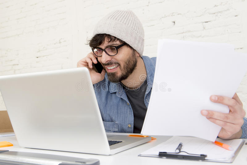 Hispanic attractive hipster businessman working at home office using mobile phone. Corporate portrait of young Hispanic attractive hipster businessman on his 30s royalty free stock image