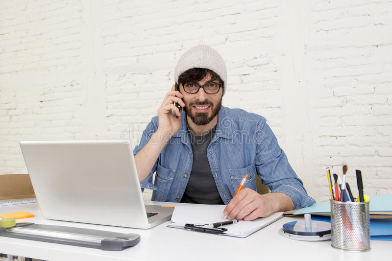 Hispanic attractive hipster businessman working at home office using mobile phone. Corporate portrait of young Hispanic attractive hipster businessman on his 30s royalty free stock photos