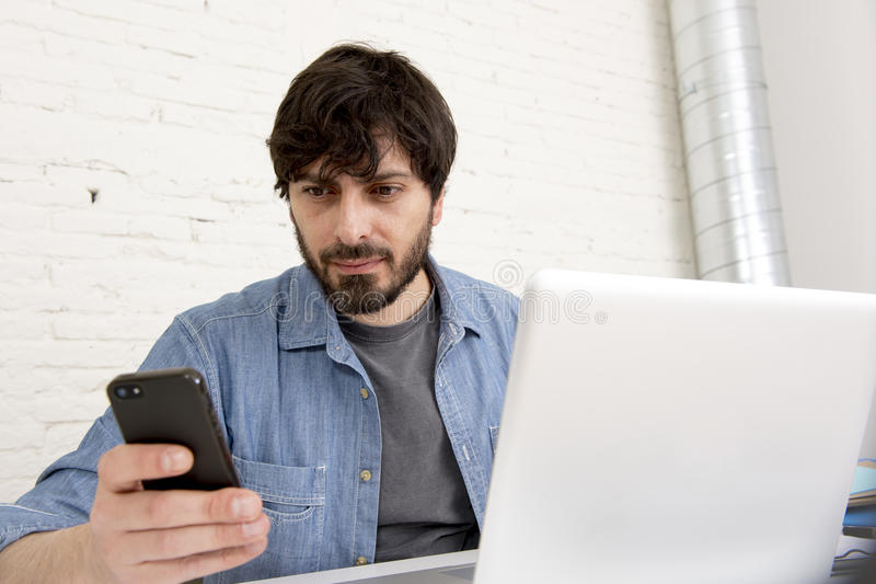 Hispanic attractive hipster businessman working at home office using mobile phone. Corporate portrait young Hispanic attractive hipster businessman on his 30s stock photo