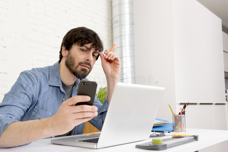 Hispanic attractive hipster businessman working at home office using mobile phone. Corporate portrait young Hispanic attractive hipster businessman on his 30s royalty free stock image