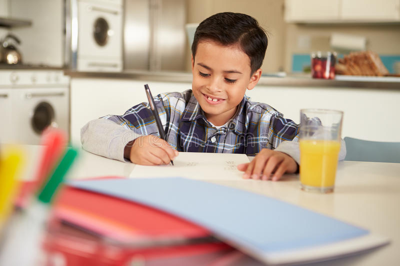 Hispanic Boy Doing Homework At Table. In Kitchen Writing In Book stock photo