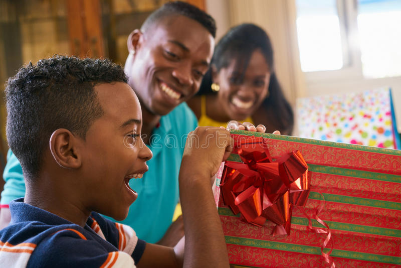 Hispanic Boy Opening Gift Box Happy Black Child Celebrating Birthday. Happy black family at home. African american father, mother and child celebrating birthday stock image