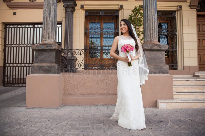 Hispanic bride outside a courthouse. Full length view of a Hispanic bride waiting outside a courthouse and looking towards copy space stock photos