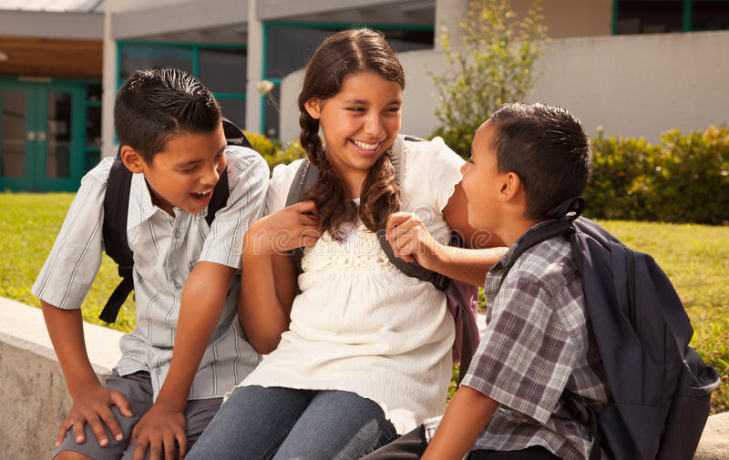Hispanic Brothers and Sister Talking Ready for School stock photo