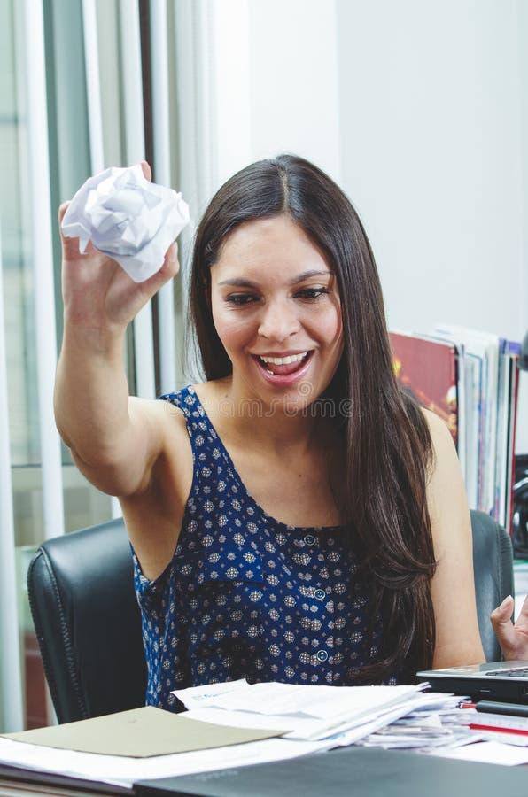 Hispanic brunette sitting by office desk holding stock photo