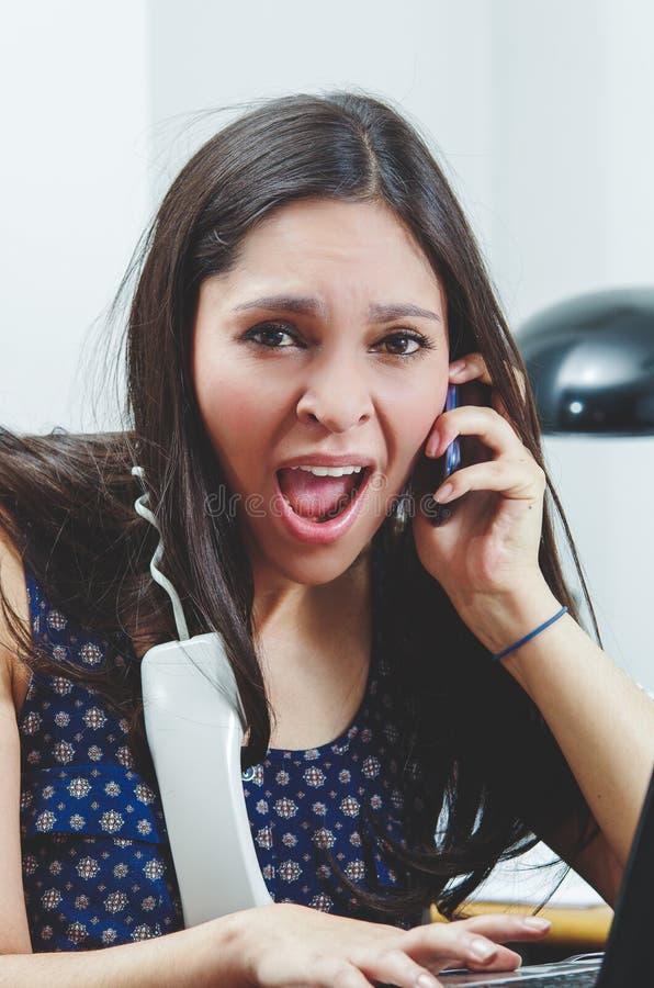 Hispanic brunette sitting by office desk talking stock photos