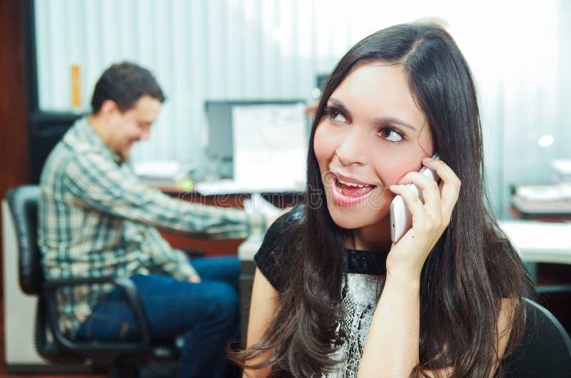 Hispanic brunette sitting by office desk talking royalty free stock image