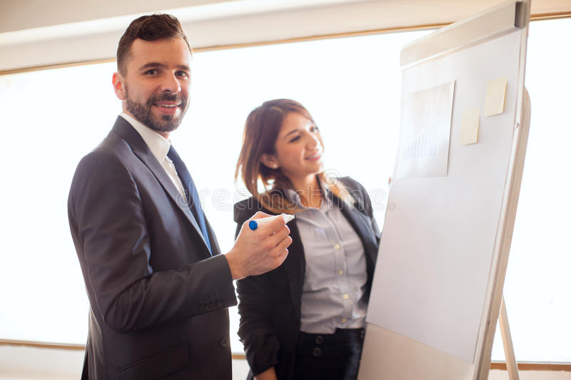 Hispanic business executives at work. Portrait of a couple of young Hispanic business executives doing some work on a flipchart during a business trip and stock images