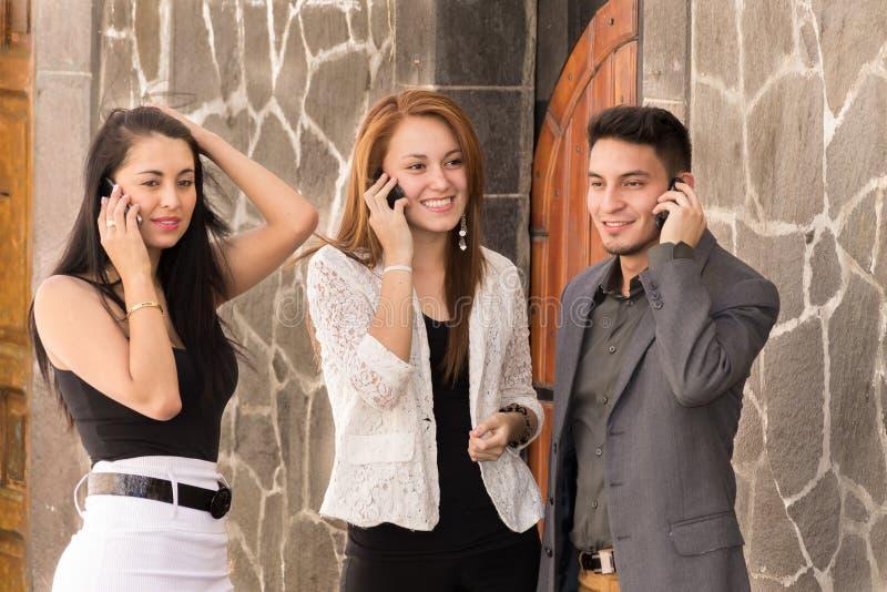 Hispanic business people talking on phone outside stock images