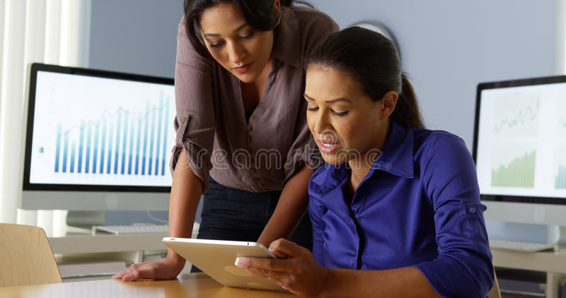 Hispanic business women working with colleague on tablet computer royalty free stock image