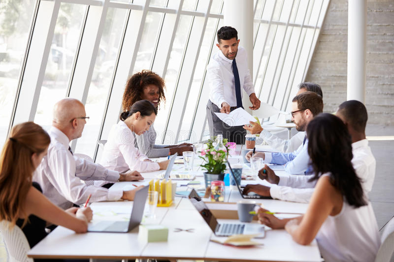 Hispanic Businessman Leading Meeting At Boardroom Table royalty free stock photography