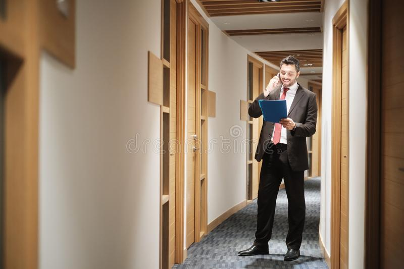 Hispanic Businessman At Work As Manager Talking On Cell Phone. Happy businessman working in office corridor, financial consultant talking on mobile telephone and royalty free stock photo