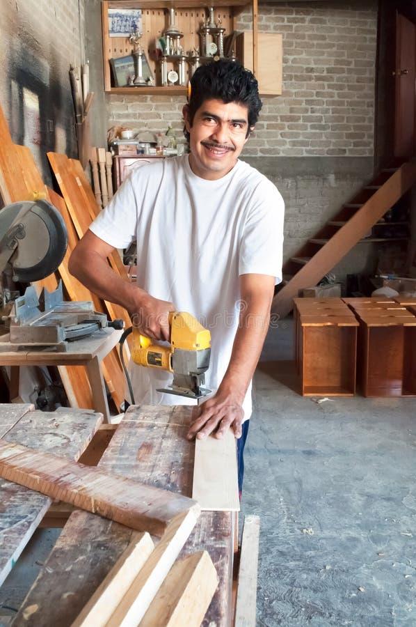 Hispanic carpenter. Carpenter working wood in a Latin carpentry royalty free stock image