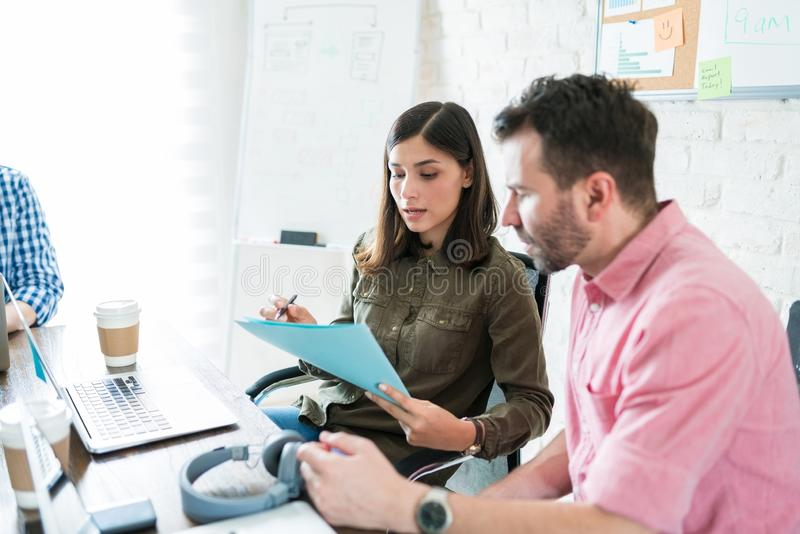 Businesswoman Reading Documents To Coworker In Workplace. Hispanic colleagues discussing over documents in meeting at office royalty free stock images