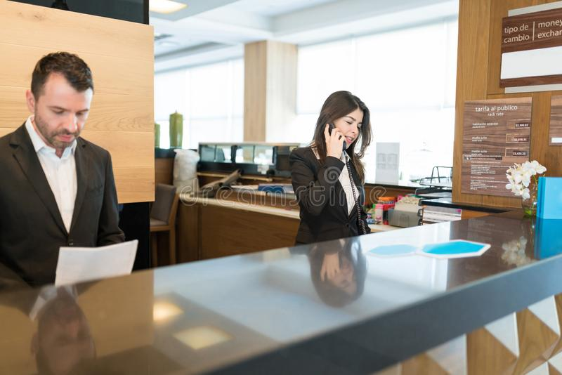 Hispanic Colleagues Working At Hotel. Female clerk answering phone while standing by male coworker at reception desk in lobby stock images