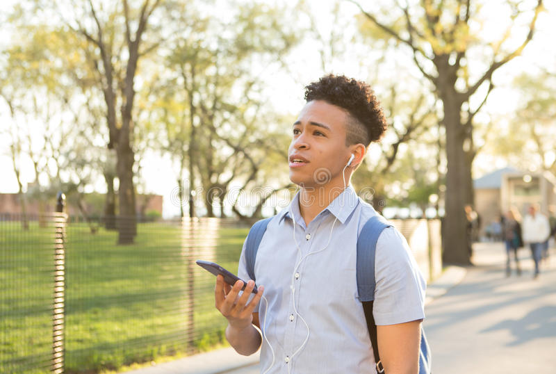 Hispanic college student talks on the smartphone with earbuds royalty free stock images