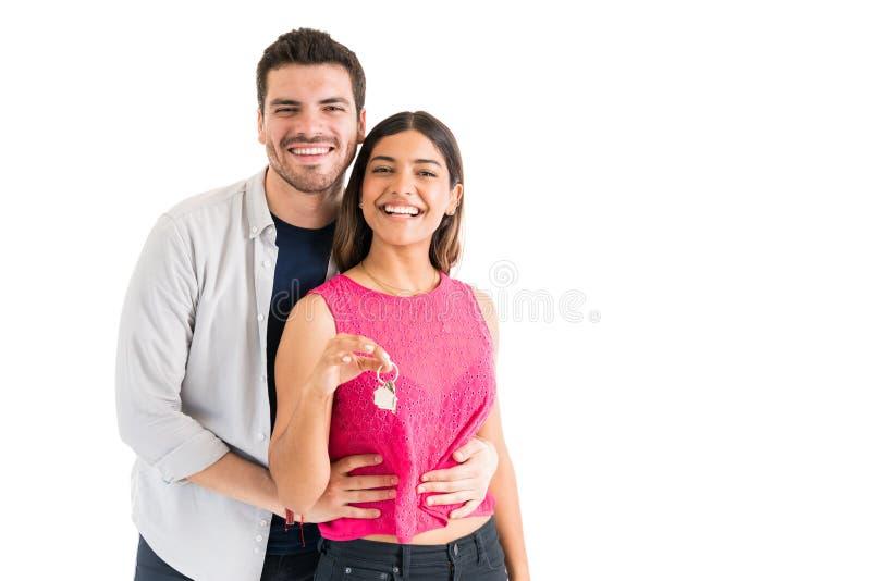 Hispanic Couple With Keys Against Plain Background royalty free stock images