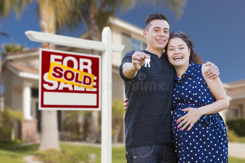 Hispanic Couple, Keys, New Home and Sold Real Estate Sign royalty free stock photos