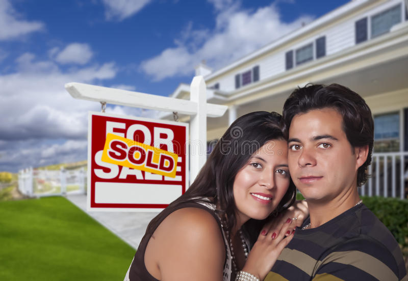 Hispanic Couple, New Home and Sold Real Estate Sign royalty free stock photos