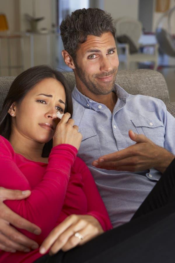 Hispanic Couple On Sofa Watching Sad Movie On TV stock images