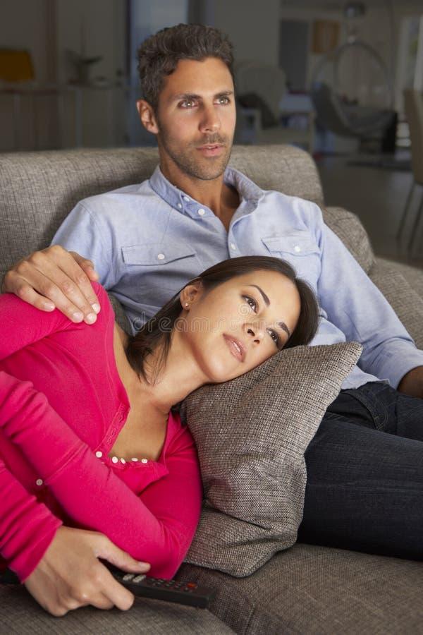 Hispanic Couple On Sofa Watching TV stock image