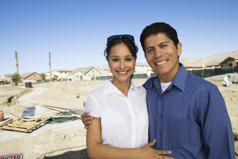 Hispanic Couple Standing At Construction Site stock photo