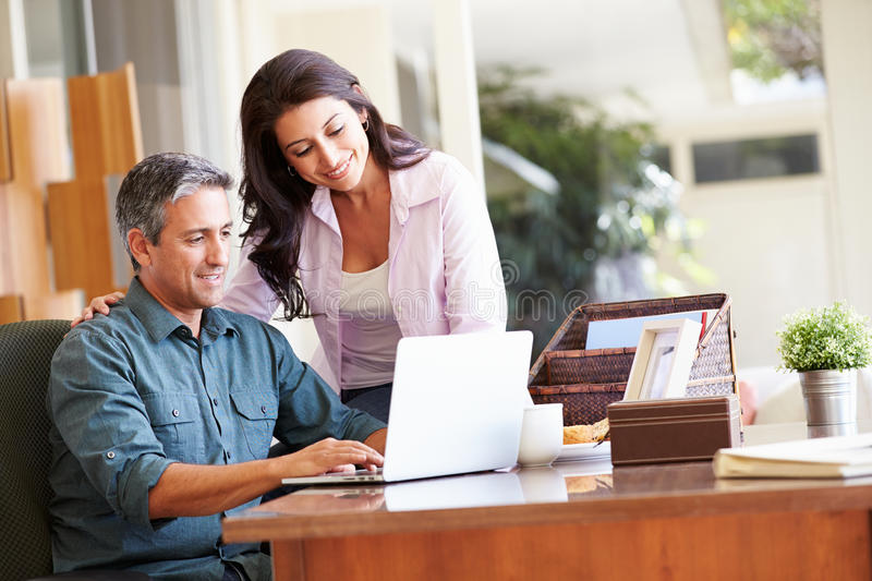 Hispanic Couple Using Laptop On Desk At Home. Browsing The Net stock image