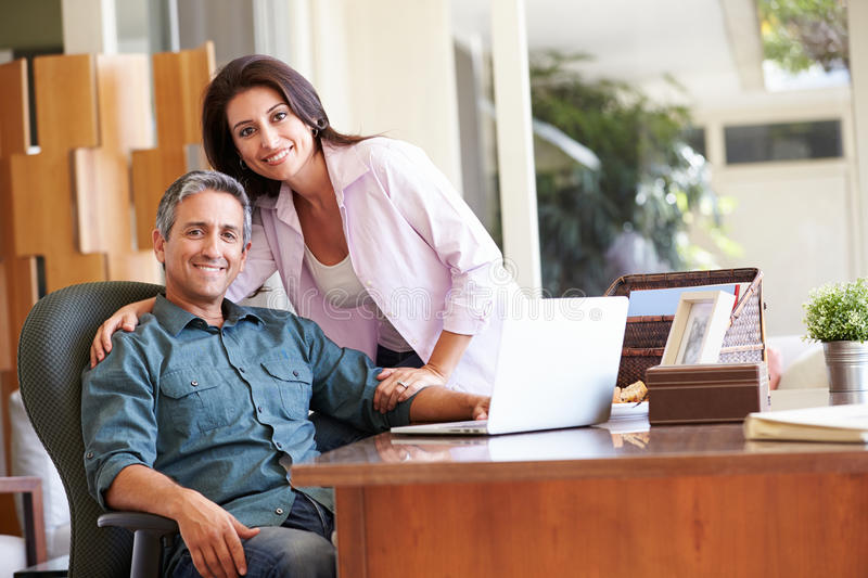 Hispanic Couple Using Laptop On Desk At Home. Looking At Camera Smiling stock image