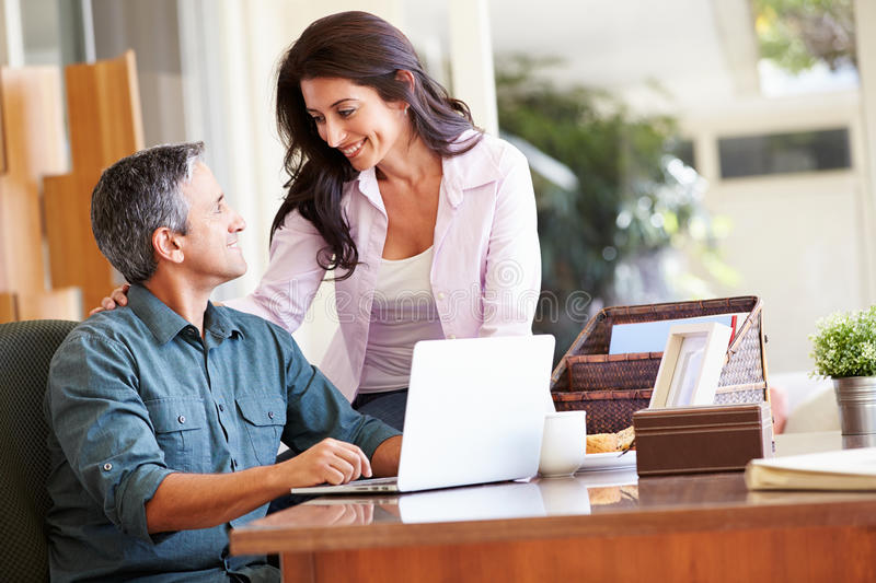 Hispanic Couple Using Laptop On Desk At Home. Smiling At Each Other royalty free stock images