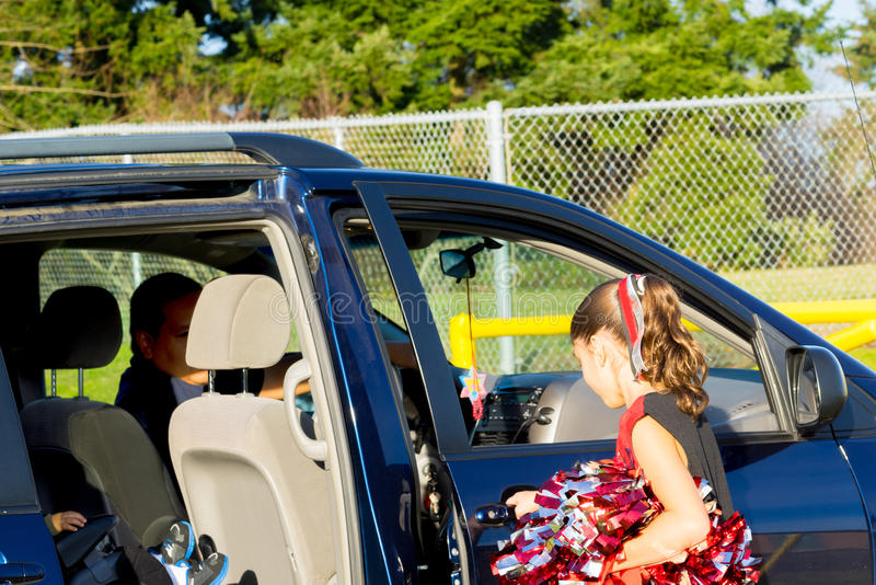 Hispanic Dad Picks Up Daughter After Cheerleader Practice royalty free stock image