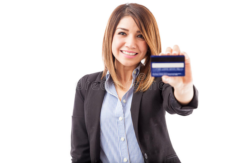 Hispanic executive with a credit card. Portrait of a gorgeous young Hispanic woman in a suit handing over a credit card and smiling stock photo